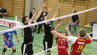 Marcin Malicki (l., Nummer 10) und Leandro Gerber (M., 20) blocken gegen Chênois' Angriff.
