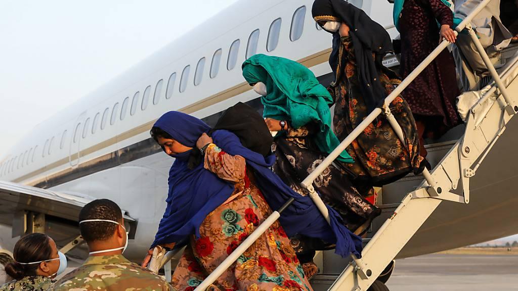 HANDOUT - Mitglieder des US-Militärs helfen afghanischen Familien bei der Ankunft auf der Naval Air Station Sigonella (NAS) aus dem Flugzeug. Foto: Mc2 Claire Dubois/U.S. Navy/Zuma Press/dpa - ACHTUNG: Nur zur redaktionellen Verwendung und nur mit vollständiger Nennung des vorstehenden Credits