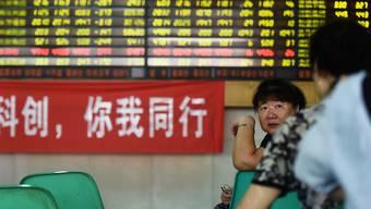 Investorinnnen unterhalten sich vor einem Werbebanner, der bei einem Börsenmarkler in Hangzhou in der ostchinesischen Provinz Zhejiang den neu lancierten Star Market anpreist.