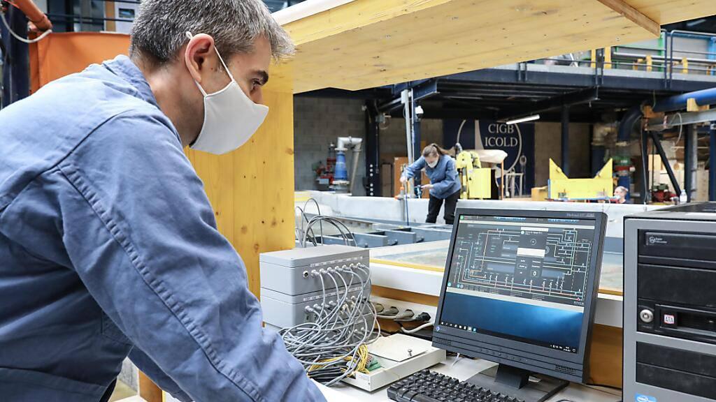Ein Mitarbeiter der EPFL-Abteilung Plattform für hydraulische Bauwerke (PL-LCH) prüft in  der Computersimulation , wie der geplante Massongex-Bex-Rhône-Damm optimal zu dimensionieren ist: Ziel ist ein Maximum an Energiegewinnung bei einem Minimum an Umwelt-Beeinträchtigung. (Pressebild)