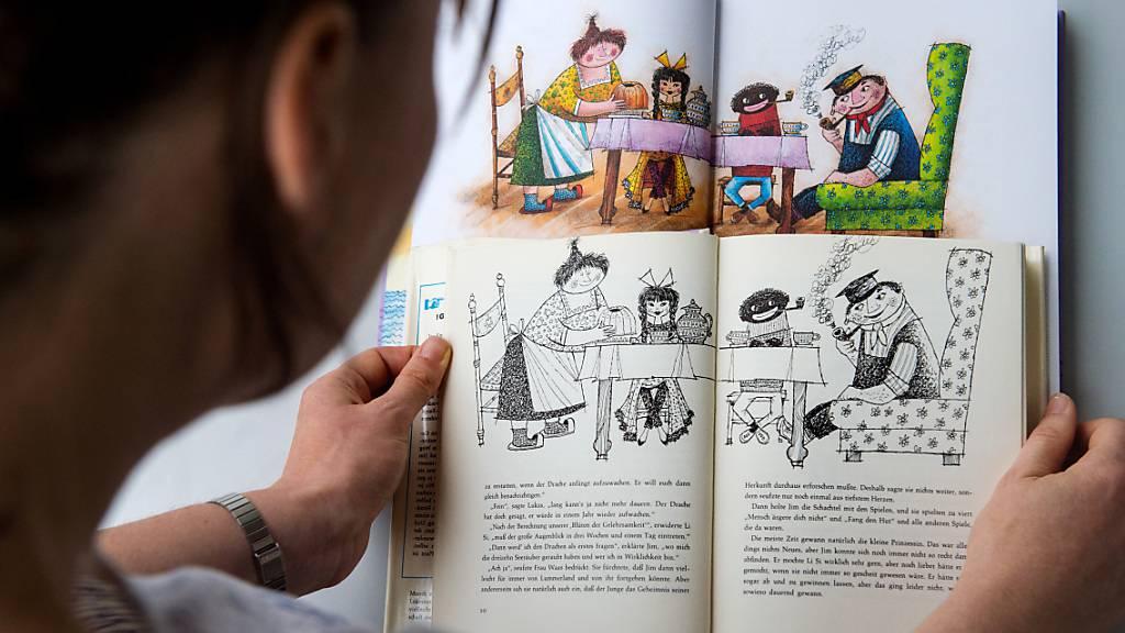 ARCHIV - Eine Frau hält in Stuttgart eine alte (vorn) und eine neue Ausgabe des Kinderbuchs «Jim Knopf und die wilde 13» des Autors Michael Ende in den Händen. Foto: picture alliance / dpa