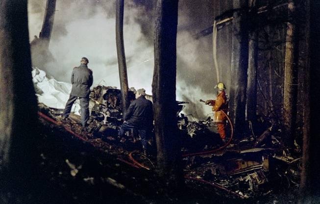 Einsatzkräfte löschen das Feuer. Die Menschen in der Maschine kamen alle ums Leben.