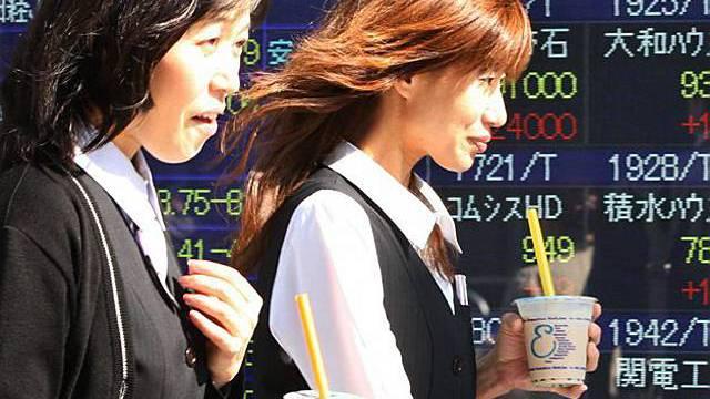 Passanten vor Tafel mit Börsenkursen in Tokio