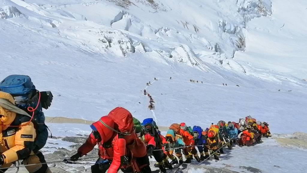 ARCHIV - In einer langer Schlange klettern Bergsteiger auf einem Pfad knapp unterhalb von Lager vier. Trotz Pandemie gibt es auf dem Mount Everest einen Besucherrekord. Foto: Rizza Alee/AP/dpa