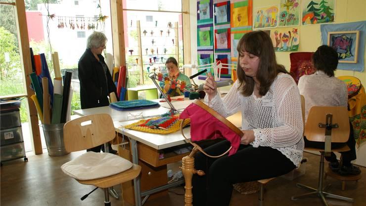 Klienten der Stiftung Lebenshilfe zeigen Besuchern ihre Arbeiten.