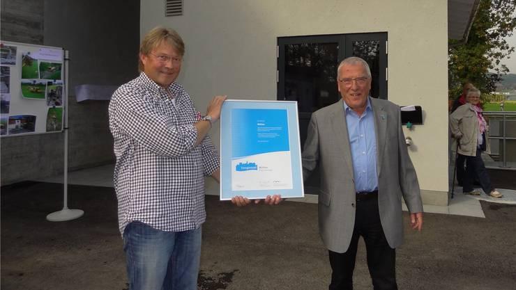 Gemeindeammann Martin Heller (links) erhält von Walter Kubik vor dem neuen Abwasserpumpwerk die Urkunde: Mühlau ist jetzt eine Energiestadt. CHR
