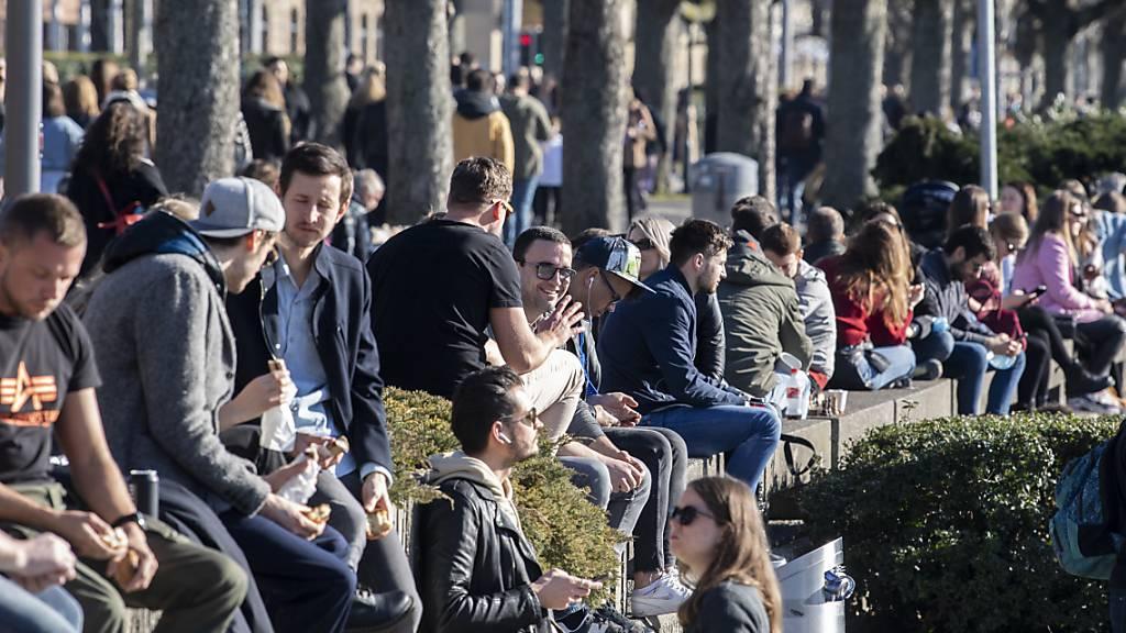 Menschen geniessen das frühlingshafte Wetter am See in Zürich.