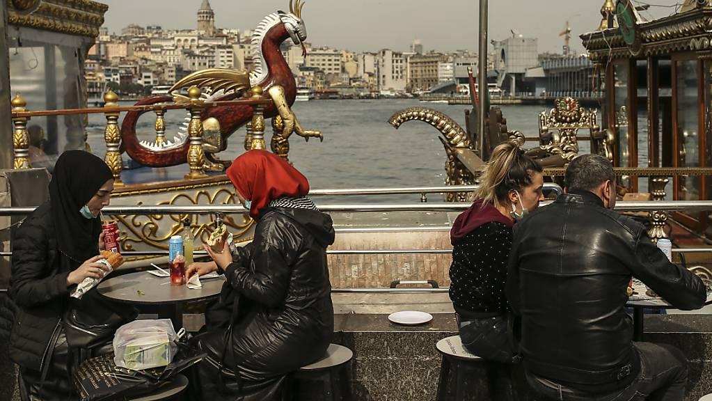 Menschen essen an Tischen am Ufer vom Goldenen Horn auf dem Eminonu Markt in Istanbul. Foto: Emrah Gurel/AP/dpa