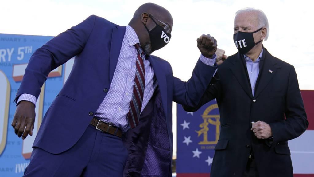 Joe Biden (r), gewählter Präsident der USA, steht während einer Wahlkampfveranstaltung in Atlanta neben dem demokratischen Kandidaten für den US-Senat, Raphael Warnock, auf der Bühne. Foto: Carolyn Kaster/AP/dpa
