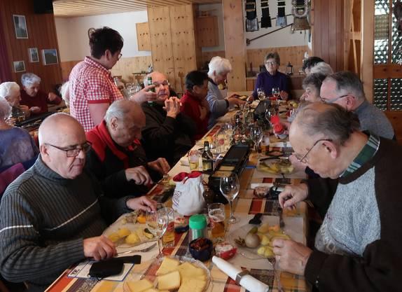 Raclette-Schmaus mit reichhaltigen Beilagen an langen Tischen