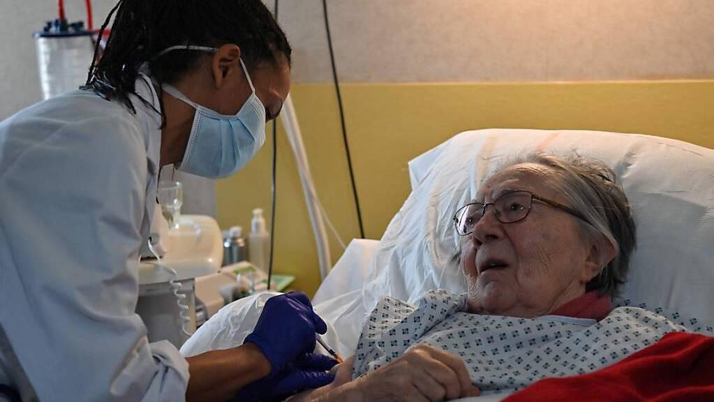 Eine Ärztin verabreicht einer älteren Frau in Frankreich eine Dosis des Corona-Impfstoffs von Pfizer-BioNTech. In der ersten Woche nach dem Impfstart am 27. Dezember gab es in Frankreich Medien zufolge nur einige Hundert Impfungen. Foto: Pascal Guyot/AFP/dpa