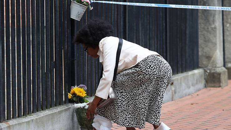 Eine Frau legt im Stadtzentrum von Reading Blumen nieder. Foto: Jonathan Brady/PA Wire/dpa