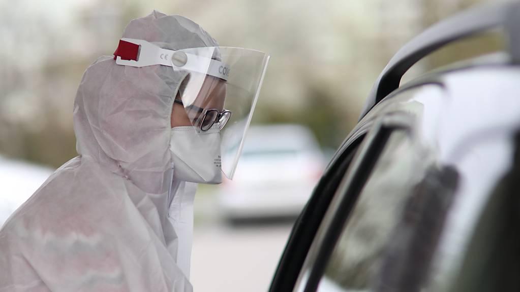 ARCHIV - Ein medizinischer Mitarbeiter im Schutzanzug und mit Gesichtsschutz nimmt in einem mobilen diagnostischen Labor in Warschau Proben von einem Patienten entgegen. Foto: Leszek Szymanski/PAP/dpa