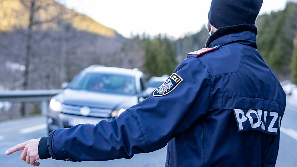 Ein Polizist kontrolliert Fahrzeuge auf einer Straße nahe Kitzbühel. Tirol verlängert die Pflicht zu Corona-Ausreisetests. Foto: Expa/Johann Groder/APA/dpa