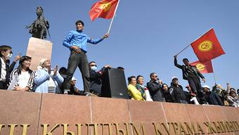 Menschen protestieren während einer Kundgebung gegen die Ergebnisse einer Parlamentsabstimmung. Nach der Parlamentswahl in dem zentralasiatischen Land Kirgistan ist es zu Ausschreitungen mit der Polizei gekommen. Foto: Vladimir Voronin/AP/dpa