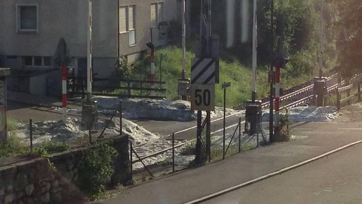 Der Bahnübergang an der Stadtbachstrasse/Sonnmattstrasse am Donnerstagmorgen nach dem Sturm: Noch immer sieht man die Hagelmassen.