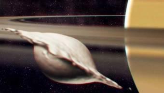 Entstehung von Atlas, einem der kleinen, inneren Monde des Saturns. Seine flache, ravioliartige Form kam bei der Kollision und Verschmelzung zweier gleich grosser Körper zustande. Die Illustration zeigt einen Moment, bevor die Neuausrichtung des Mondes aufgrund der Gezeiten abgeschlossen ist.