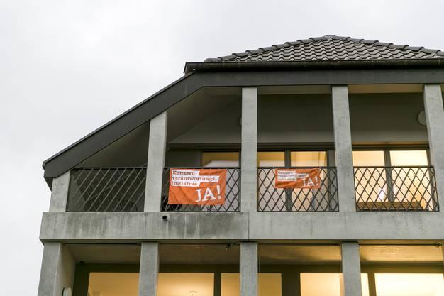 Am Gebäude der katholischen Landeskirche in Aarau hängen zwei Flaggen der Konzernverantwortungsinitiative.