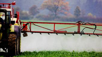 Ein Bauer versprüht Pflanzenschutzmittel auf einem Feld.