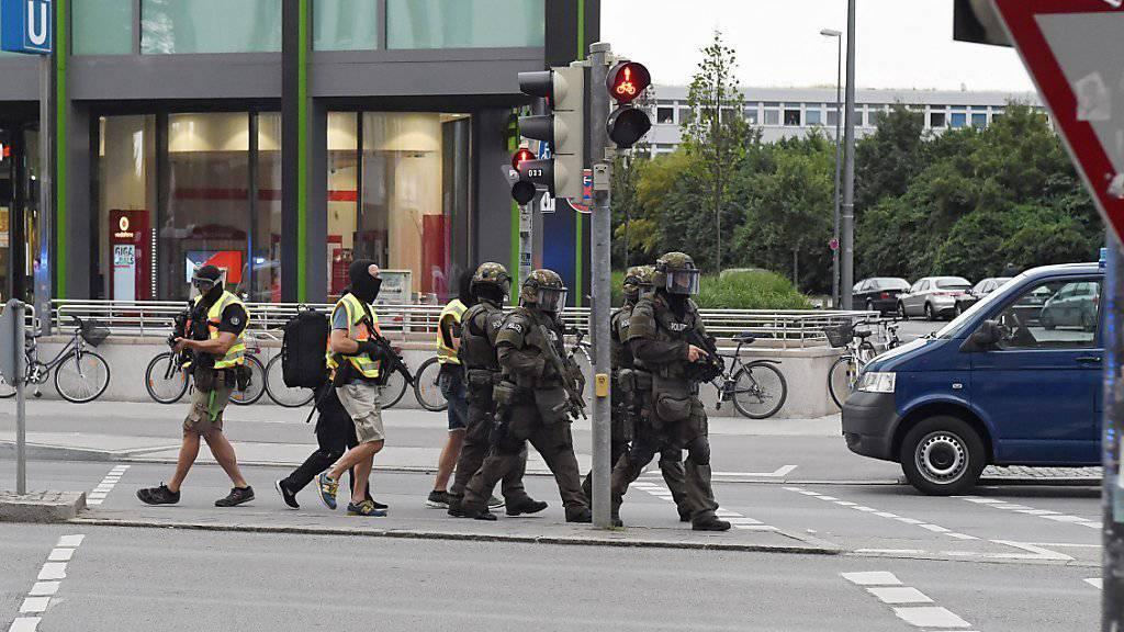 Nach der Schiesserei mit mehreren Toten in einem EInkaufszentrum in München patrouillieren Spezialeinheiten der Polizei vor dem Gebäude.