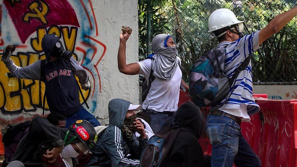 Studenten werfen Steine bei Protesten gegen den venezolanischen Präsidenten Maduro in Caracas. Sie fordern sofortige Neuwahlen.