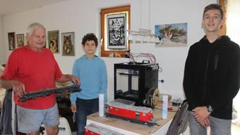 Die Jugendlichen werden in die Geheimnisse des 3D-Druckers (im Hintergrund) eingeführt.