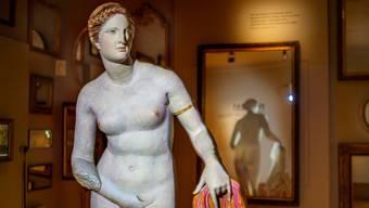Entblössende Lichtspiele führen im Museum ins Thema ein: Ein Gipsabguss einer römischen Marmorkopie einer griechischen Aphrodite wird so beleuchtet, dass die steinern neutrale Skulptur mit Farbe zur nackten Frau wird, sich eine Hand vor die Scham hält und am Ende schwarze Zensurbalken bekommt.