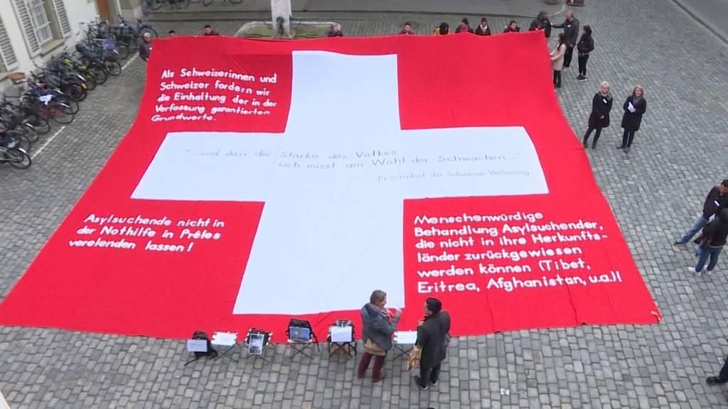 Mit riesiger Schweizerfahne gegen Rückkehrzentrum in Prêles