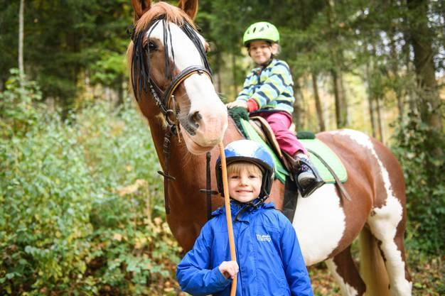 Die Kinder führten einender auf und neben dem Pferd