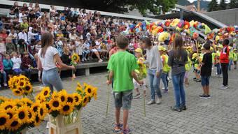Die Jüngsten werden von den Sechstklässlern mit einer Sonnenblume begrüsst.