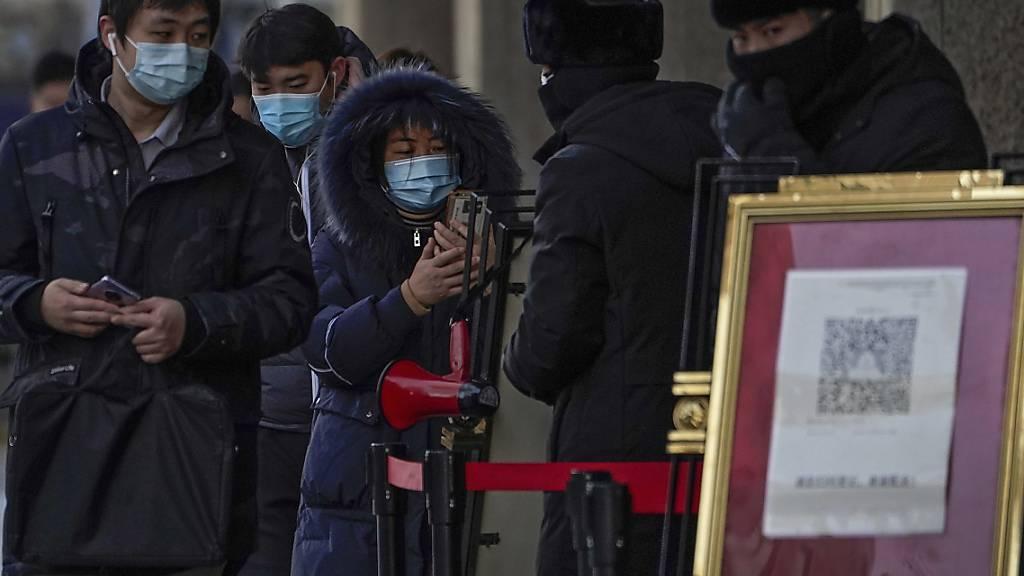 Menschen, die Gesichtsmasken tragen, scannen mit ihren Smartphones einen Code, bevor sie ein Bürogebäude betreten. Foto: Andy Wong/AP/dpa
