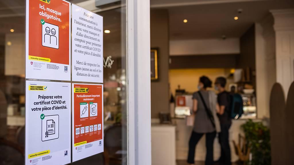 Ein Plakat informiert Gäste eines Restaurants in Genf über die geltenden Massnahmen zur Eindämmung des Coronavirus. (Themenbild)