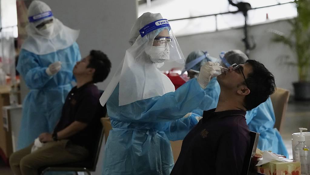 Angestellte eines Einkaufszentrums in Bangkok unterziehen sich einem Corona-Test. Thailands Regierung will trotz weiterhin hoher Corona-Zahlen an einer weitgehenden Öffnung des Landes ab Oktober festhalten. Das teilte der Tourismusminister Phiphat Ratchakitprakar laut Angaben der «Bangkok Post» mit. Foto: Sakchai Lalit/AP/dpa