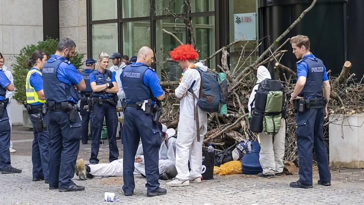 Viel Holz vor der Hütte: Polizisten räumen die Blockade der Aktivisten des Klimacamps der Gruppe Collective Climate Justice vor der Bank UBS am Aeschenplatz in Basel.