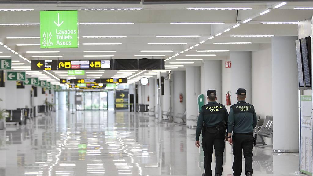 Zwei Zivilbeamte patrouillieren am Flughafen Palma de Mallorca. Wegen wieder anziehender Corona-Zahlen hat die Regionalregierung Mallorcas die Maßnahmen gegen die Ausbreitung des Coronavirus über Weihnachten verschärft. Foto: Isaac Buj/EUROPA PRESS/dpa