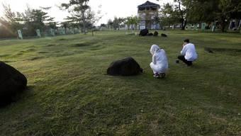 Betende am Samstag in der indonesischen Provinz Aceh am Massengrab Ulee Lheue für Tsunami-Opfer.