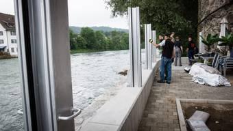 Ein Schutz-Wall für Bremgarten: Als erstes schrauben die Feuerwehrmänner die Aluminiumsäulen auf das Betonfundament.