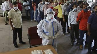 Mitarbeiter einer Universität stehen in der Stadt Jammu Schlange, um sich für einen Corona-Test anzumelden. Indien ist weltweit momentan das am zweitstärksten vom Coronavirus betroffene Land. Foto: Channi Anand/AP/dpa