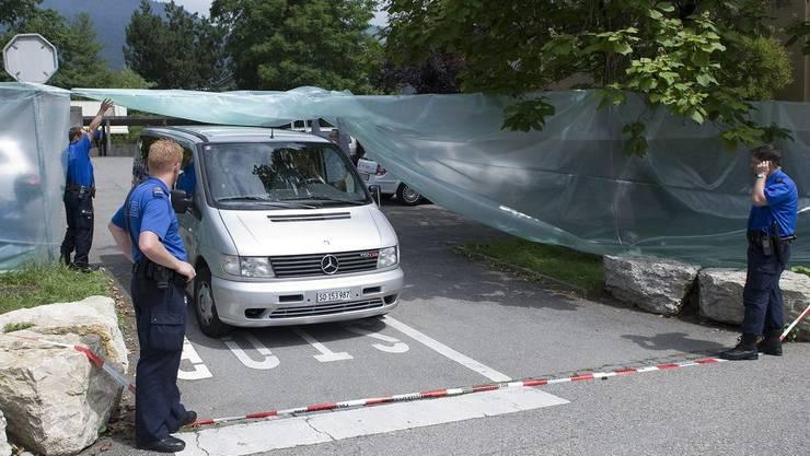 Ein Leichenwagen verlässt den Tatort.