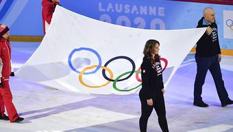 Die Olympische Fahne in der Eisarena Malley, gezogen von Diidier Cuche und Florence Schilling