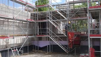 Hinter den Gerüststangen entsteht das neue Schulhaus Zehntenhof. Die Öffnung hinter den Treppen trennt die beiden Gebäudekörper.