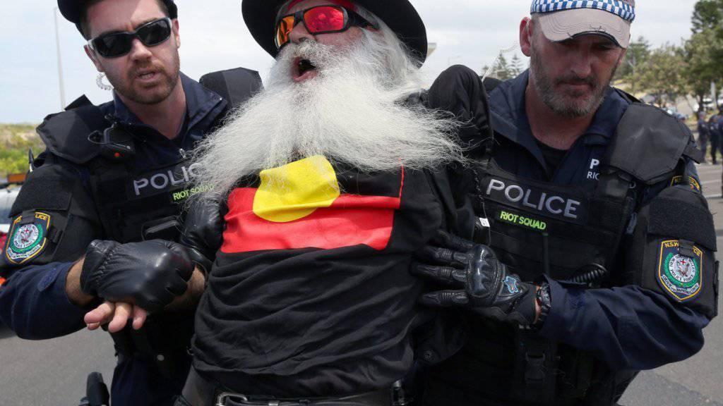 Nach Handgreiflichkeiten zwischen linken Demonstranten und Islamgegnern am Rande einer Kundgebung in Sydney zum Gedenken an fremdenfeindliche Ausschreitungen vor zehn Jahren nehmen Polizisten einen Mann fest.