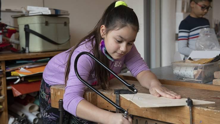 Konzentriert schneidet Serena eine Form aus. Mit der Laubsäge folgt sie den Bleistiftlinien auf der Sperrholzplatte.