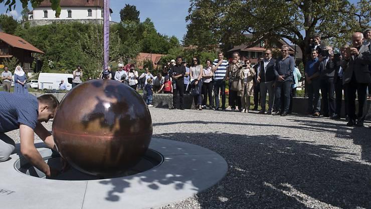 Die versiegelte Kupferkugel mit den Gedanken aus dem Bruder-Klaus-Gedenkjahr wird auf dem Dorfplatz von Flüeli in einen Schacht eingelassen.