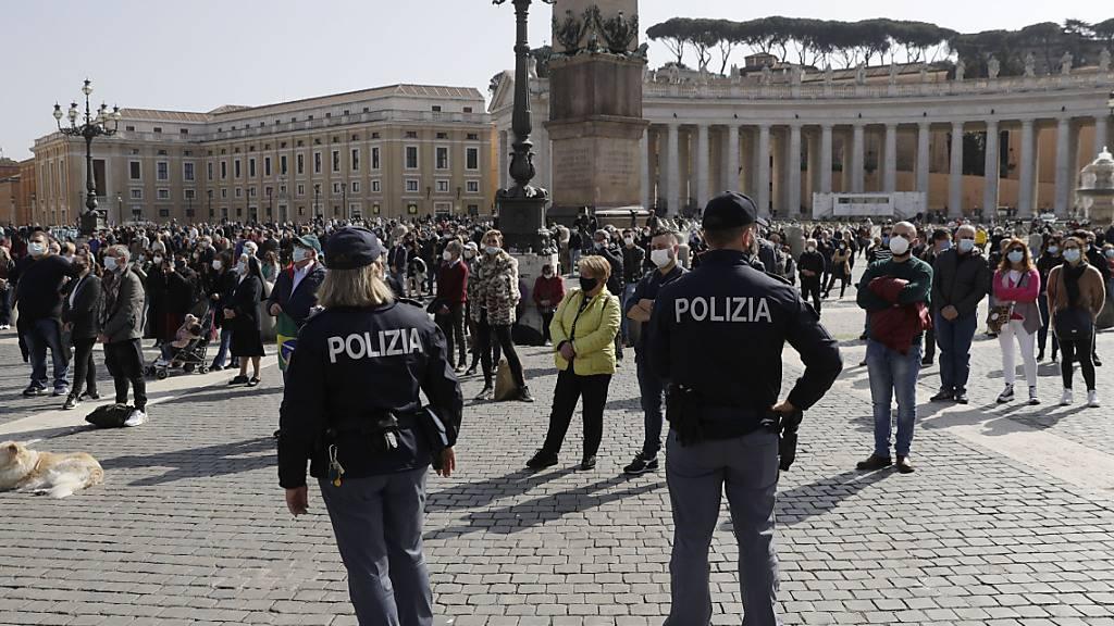 Italienische Polizisten patrouillieren auf dem Petersplatz während des Angelus-Mittagsgebets von Papst Franziskus. Neben einer Katechese richtet er meist auch ein Grußwort an die Gläubigen. Foto: Gregorio Borgia/AP/dpa