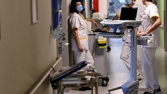 Krankenhauspersonal mit Mund-Nasen-Bedeckung bereitet in Bonheiden die Öffnung einer zusätlich eingerichteten Intensivstation vor. Foto: Dirk Waem/BELGA/dpa