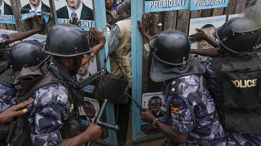Polizisten versuchen das Tor des Parteisitzes von Oppositionskandidat Besigye zu schliessen.