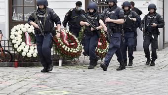 Polizisten am Tag nach dem Anschlag nahe des Tatorts. Foto: Hans Punz/APA/dpa