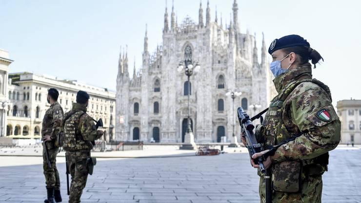 Italienische Armeeangehörige sorgen vor dem Mailänder Dom dafür, dass die Ausgangssperre eingehalten wird. (Bild: Keystone)