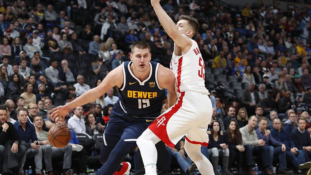 Denvers Center Nikola Jokic (links) zieht an Houstons Center Isaiah Hartenstein vorbei zum Korb.